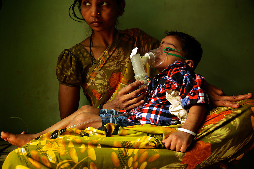 Child using nebuliser by lying mother's lap