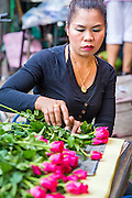 09 OCTOBER 2012 - BANGKOK, THAILAND: A vendor packages roses at the Bangkok Flower Market. The Bangkok Flower Market (Pak Klong Talad) is the biggest wholesale and retail fresh flower market in Bangkok. It is also one of the largest fresh fruit and produce markets in the city. The market is located in the old part of the city, south of Wat Po (Temple of the Reclining Buddha) and the Grand Palace.    PHOTO BY JACK KURTZ