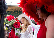A couple of young women wearing hats stand by a crowd of people watching the hat contest unfold the day of the Kentucky Derby at Santa Anita Park.