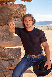 hot cowboy leaning against a rustic cabin