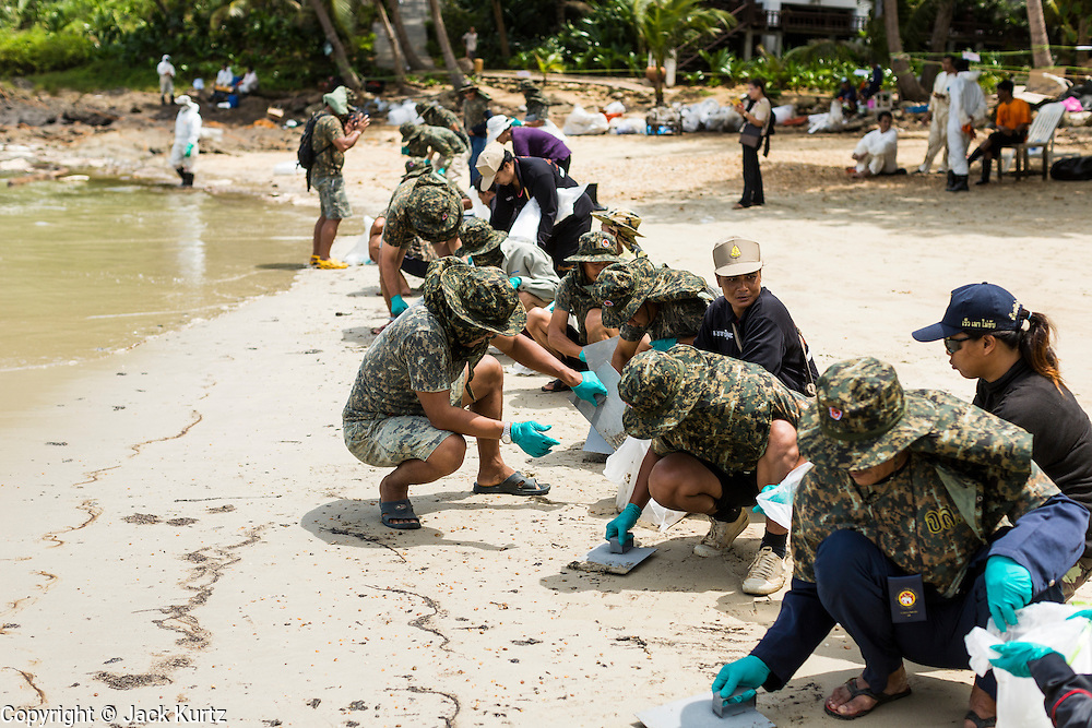 02 AUGUST 2013 - KOH SAMET, RAYONG, THAILAND: Royal Thai Marines clean a section of Ao Prao beach on Koh Samet island Friday after an oil spill fouled the beach. About 50,000 liters of crude oil poured out of a pipeline in the Gulf of Thailand over the weekend authorities said. The oil made landfall on the white sand beaches of Ao Prao, on Koh Samet, a popular tourist destination in Rayong province about 2.5 hours southeast of Bangkok. Workers from PTT Global, owner of the pipeline, up to 500 Thai military personnel and volunteers are cleaning up the beaches. Tourists staying near the spill, which fouled Ao Prao beach, were evacuated to hotels on the east side of the island, which was not impacted by the spill. Officials have not said when Ao Prao beach would reopen. PTT Global Chemical Pcl is part of state-controlled PTT Pcl, Thailand's biggest energy firm.    PHOTO BY JACK KURTZ