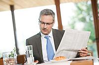 Österreich, Geschäftsmann macht Pause in Restaurant, Zeitung lesend und Tablet Computer nutzend
