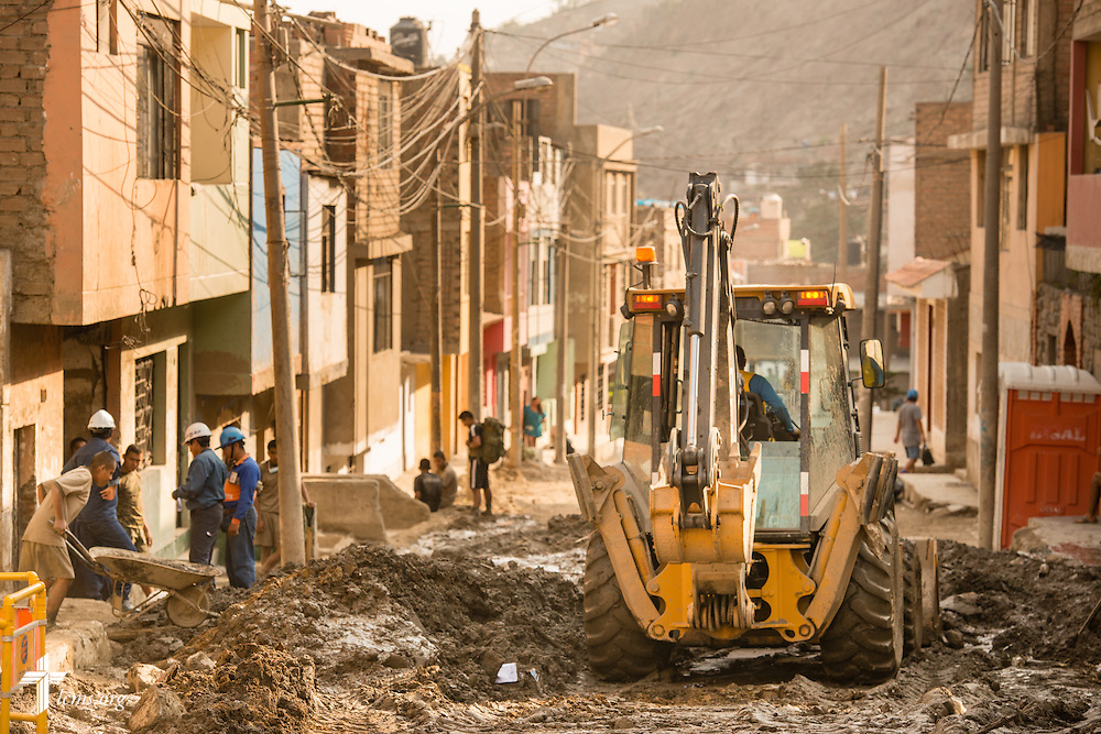 Workers clear mud from homes and businesses near Lima, Peru, on Tuesday, April 7, 2015. Heavy rains in March caused massive avalanches of mud and rocks in several regions, killing residents, displacing others, and causing infrastructure destruction. LCMS Communications/Erik M. Lunsford