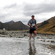 Runner Steve Robb crosses Moke Creek on the Ben Lomond High Country Station during the Pure South Shotover Moonlight Mountain Marathon and trail runs. Moke Lake, Queenstown, New Zealand. 4th February 2012. Photo Tim Clayton