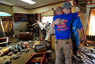 Tom Harris hugs James Aaron after Aaron tears up when he saw the flood damage to his home in the Flats. The water lines went a few feet up his roof, tearing down his ceiling in spots, both his front and rear porch have seperated from the home. Homes in this neighborhood are prone to flooding and FEMA is refusing to help the families that reside here any longer.