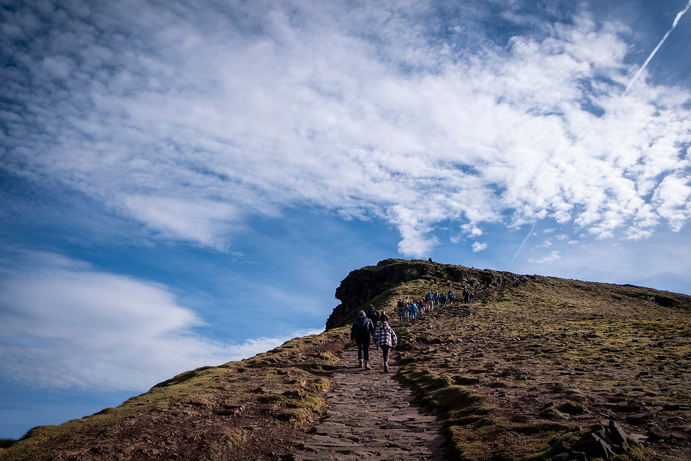 A group of adult and child ramblers walk along the dirt track towards the summit of Pen Y Fan Mountain in Brecon Beacons National Park, Wales, Powys, United Kingdom. Pen Y Fan is the highest point in the Brecon Beacons hill and mountain range in South Wales. The National Park was established in 1957 due to the spectacular landscape which is rich in natural beauty.  (photo by Andrew Aitchison / In pictures via Getty Images)