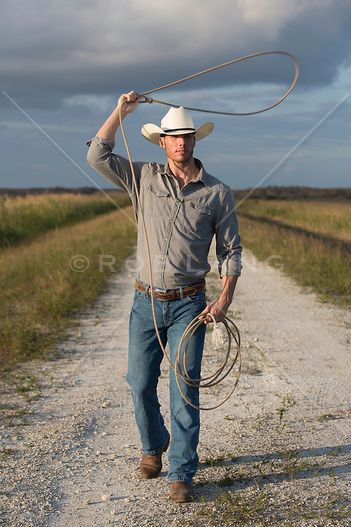 hot cowboy swinging a lasso while walking on a dirt road at sunset