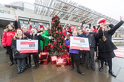 """Campaigners from Shelter Scotland raise awareness of their campaign """"Homelessness - Far From Fixed"""" outside the Scottish Parliament in Edinburgh. They are joined by carol singers from Corstorphine Primary School, a Christmas tree and a giant snakes and ladders board game - Chance Not Choice - which illustrates how life chances affect people's ability to keep a roof over their head."""