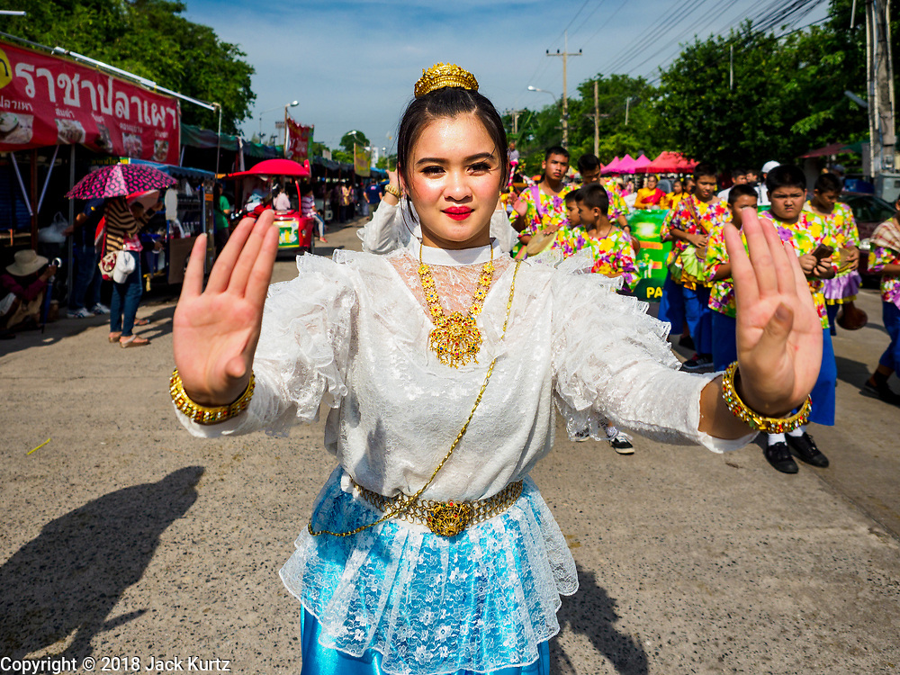 23 OCTOBER 2018 - CHONBURI, CHONBURI, THAILAND: A woman dances in the parade before the water buffalo races in Chonburi. Contestants race water buffalo about 100 meters down a muddy straight away. The buffalo races in Chonburi first took place in 1912 for Thai King Rama VI. Now the races have evolved into a festival that marks the end of Buddhist Lent and is held on the first full moon of the 11th lunar month (either October or November). Thousands of people come to Chonburi, about 90 minutes from Bangkok, for the races and carnival midway.   PHOTO BY JACK KURTZ