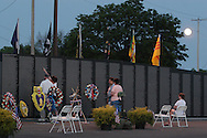Newburgh, NY - People look at the names on the Vietnam Veterans Memorial Moving wall at Stewart International Airport at the moon rises in the background on June 6, 2009.