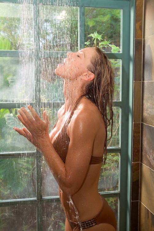 Wellness image of young woman in brown bathing suit rinsing off in shower.