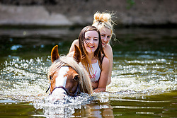 © Licensed to London News Pictures. 07/06/2018. Appleby UK. Travellers take their horses for a swim in the river at Appleby Horse Fair that started today in Appleby. The Appleby Horse fair is the biggest traditional Gypsy fair in Europe attracting 10,000 Gypsies & Travellers & 30,000 visitors. Photo credit: Andrew McCaren/LNP