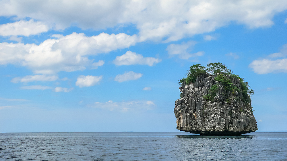 A small island stands alone, facing the open sea, its base thinned by erosion. Camarines Sur, Bicol province, Philippines, 2008.