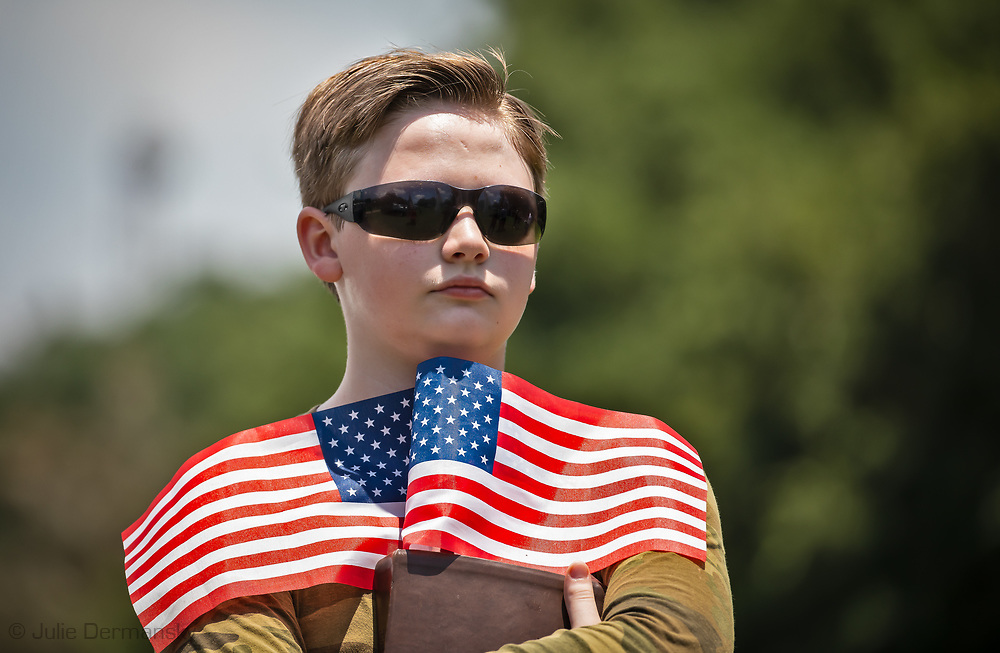 """Young boy holding american flags at a """"Save America Rally"""" in Baton Rouge on the 4th of July across the street from the Governor's Mansion where about 200 gathered. The 4th of July rally was organized by Jeff Crouer, Mimi Owens and Woody Jenkins, chairman of the executive committee for the Republican Party in East Baton Rouge Parish. Rev. Tony Spell of Life Tabernacle Church who has held church services in defiance of a stay-at-home order throughout the pandemic was one of the speakers. He an other speakers expressed their displeasure of being told to wear a mask to prevent the spread of Covid-19 and the removal of confederate monuments."""