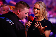 Hollywood Chris Dobey holding his baby whilst being interviewed by Sky Sports Presenter Laura Woods during the PDC World Championship darts at Alexandra Palace, London, United Kingdom on 14 December 2018.