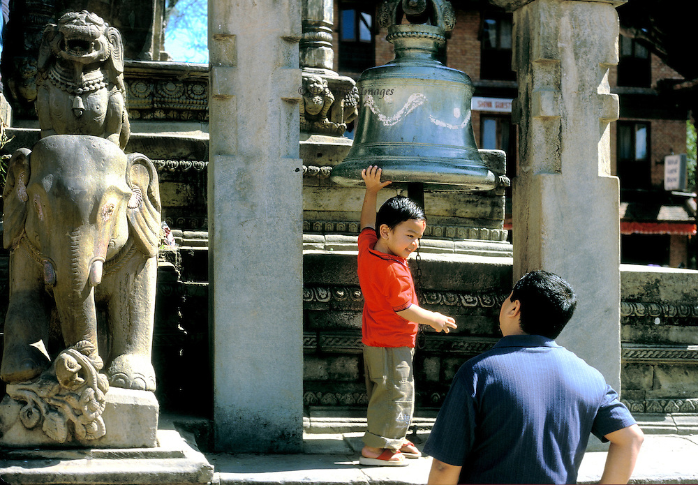 Toddler on a platform with his hand on a large bronze bell smiles at his father below.  They are in Durbar Square, Kathmandu.
