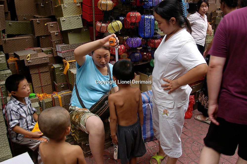 A boy has his height measured at the Beijing flea market. August 2006