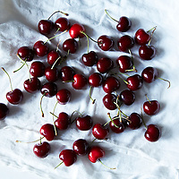 Pile of freshly cleaned cherries spread out on a white dishcloth.