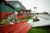 JEROME A. POLLOS/Press..Brian McComb, with Granite Enterprises Roofing, carries away a sheet of metal roofing that was removed from the top of Capone's Pub & Grill in Post Falls during the wind storm Monday.