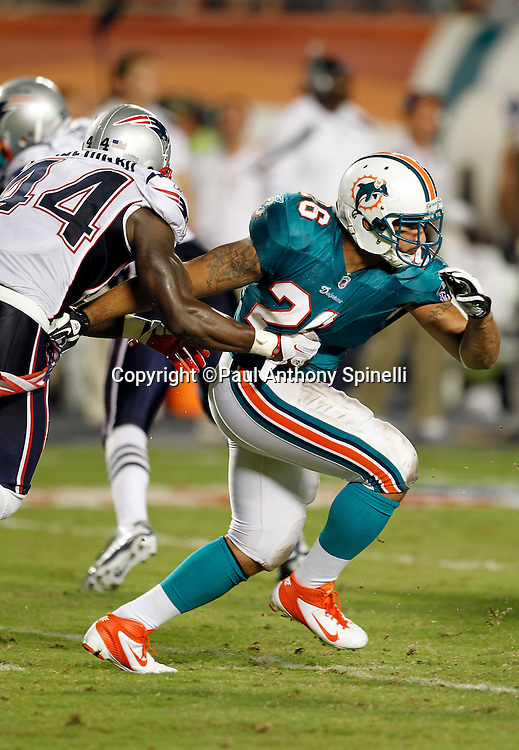 Miami Dolphins running back Lex Hilliard (26) breaks away from a jersey hold by New England Patriots defensive back James Ihedigbo (44) during the NFL week 1 football game against the New England Patriots on Monday, September 12, 2011 in Miami Gardens, Florida. The Patriots won the game 38-24. ©Paul Anthony Spinelli