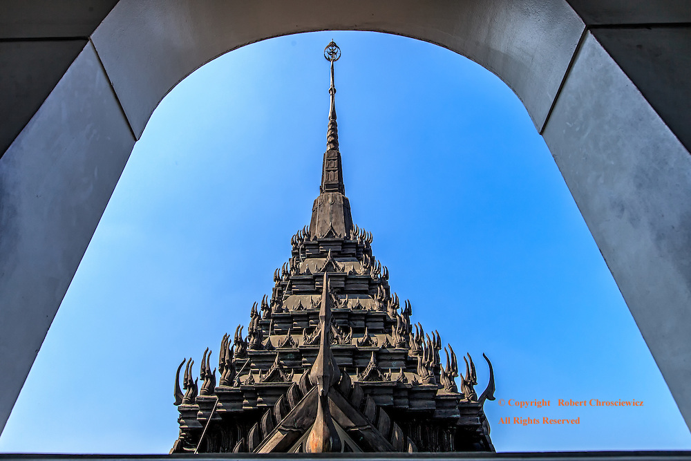 Framed Spire: From inside the temple, the deep inset of the window sill frames the scene of an ornate, multi tiered black spire, completed with numerous mystical Chofa, all set against a clear blue sky, Wat Ratchanada, Bangkok Thailand.