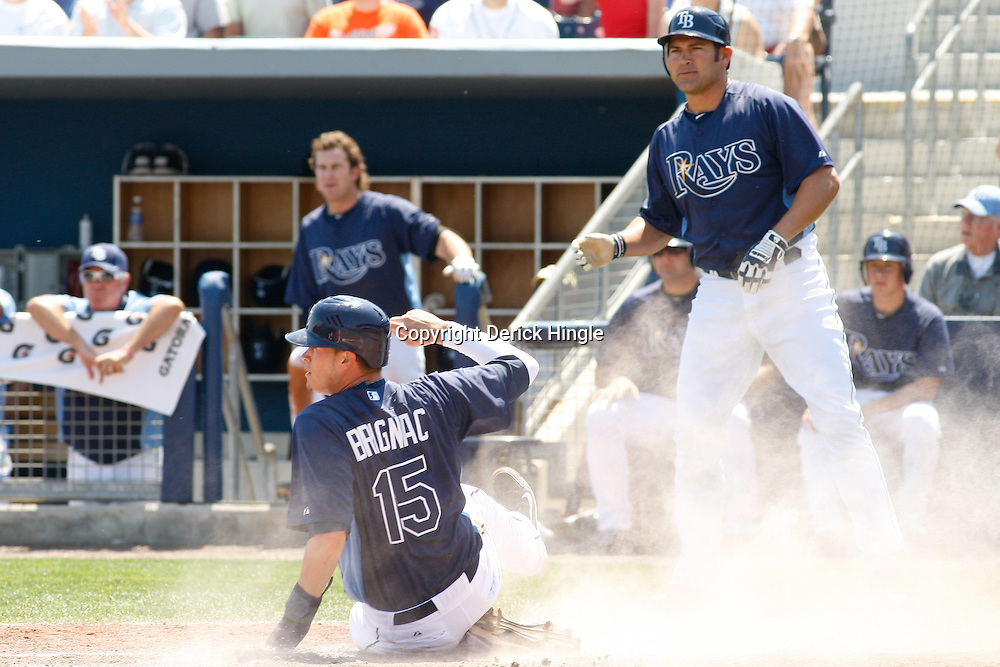 March 20, 2011; Port Charlotte, FL, USA; Tampa Bay Rays shortstop Reid Brignac (15) slides home safe during a spring training exhibition game against the Baltimore Orioles at Charlotte Sports Park.  Mandatory Credit: Derick E. Hingle-US PRESSWIRE