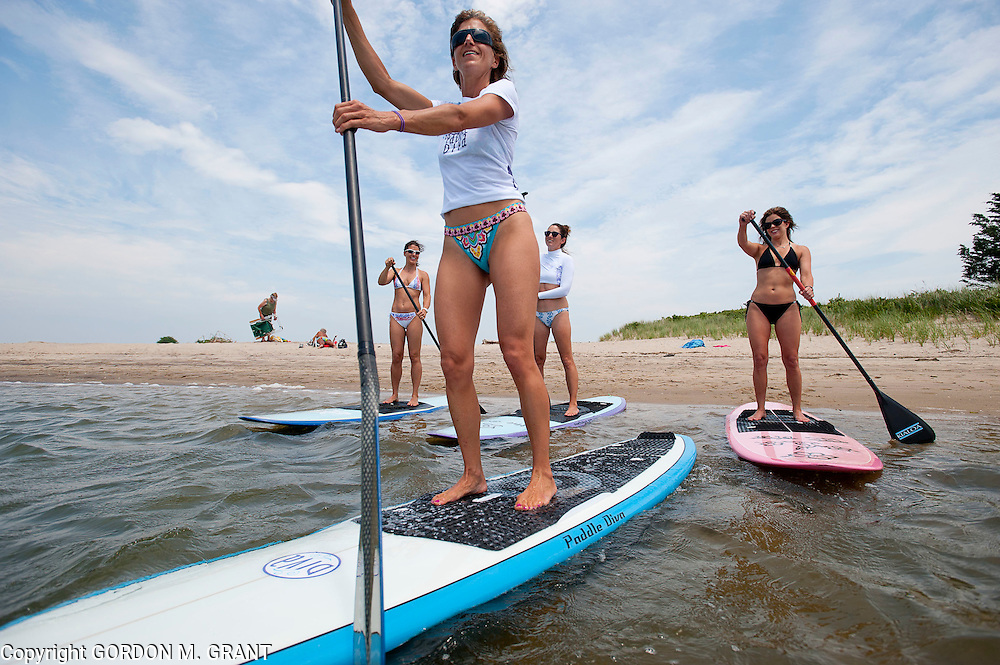 Gina Bradley, the owner of Paddle Diva, front, a paddleboard instructor, gives a lesson to (l-r) Jennifer Ford, Peri Allen and Meg Salen, at Louse Point in East Hampton.  (June 24, 2010)
