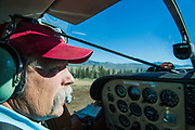 A multi-generation pilot of the Sawtooth Mountains checks to ensure the skies are clear prior to leaving the runway.