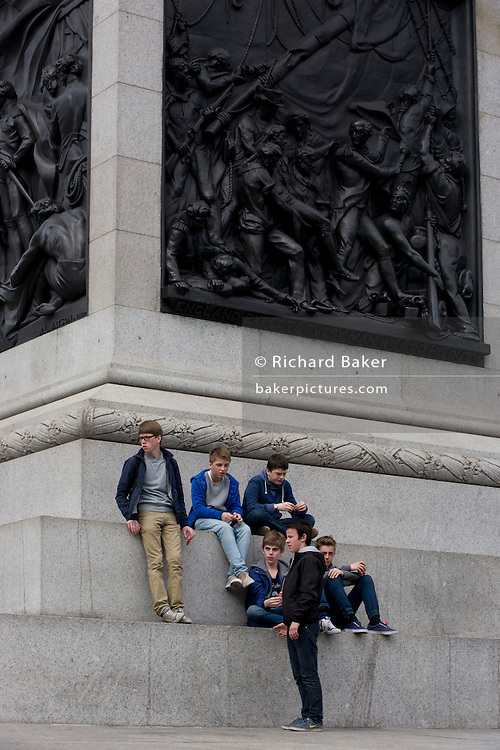 Teenagers at Trafalgar Square, sit beneath the relief on the south face of the plinth showing the Death of Nelson on Nelson's Column in Trafalgar Square.