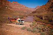 A helicopter at the Colorado river at the base of the Bridge Canyon along the west rim of the Grand Canyon National Park inside the Hualapai Indian Reservation, Arizona, USA