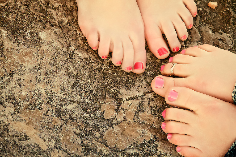 Two pairs of feet with painted toes rest on rock