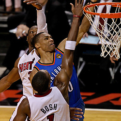 Jun 21, 2012; Miami, FL, USA; Oklahoma City Thunder point guard Russell Westbrook (0) shoots over Miami Heat power forward Chris Bosh (1) and Miami Heat shooting guard Dwyane Wade (3) during the third quarter in game five in the 2012 NBA Finals at the American Airlines Arena. Mandatory Credit: Derick E. Hingle-US PRESSWIRE