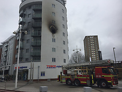 Portsmouth,Hampshire Saturday 25th February 2017 MORE than 40 firefighters tackled a severe blaze that tore through an apartment block in a busy shopping area today.<br /> Smoke was seen billowing from a fourth floor flat above a Tesco Express store in Gunwharf Quays, Portsmouth, Hants.Smoke was seen billowing from a <br /> <br /> A spokesman for Hampshire Fire and Rescue Service said nine fire engines were in attendance, with around 45 firefighters attempting to put out the flames.<br /> <br /> The spokesman added: &ldquo;We got called at 12.58pm. The fire is on the fourth floor and is believed to have started in a kitchen.&rdquo;<br /> <br /> All residents were evacuated from the building by fire crews as they fought the blaze using specialist equipment.&copy;UKNIP