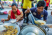 """11 MAY 2013 - BANGKOK, THAILAND: Protesters line up for breakfast. Several hundred small scale family farmers camped out """"Government House"""" (the office of the Prime Minister) in Bangkok to Thai Prime Minister Yingluck Shinawatra to deliver on her promises to improve the situation of family farmers. The People's Movement for a Just Society (P-move) is a network organization which aims strengthen the voices of different, but related causes working to bring justice for marginalized groups in Thailand, including land rights for small-scale farmers, citizenship for stateless persons, fair compensation for communities forced to relocate to accommodate large scale state projects, and housing solutions for urban slum dwellers, among others.   PHOTO BY JACK KURTZ"""