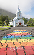 A colorfully painted rainbow road on Seydisfjordur, Iceland.