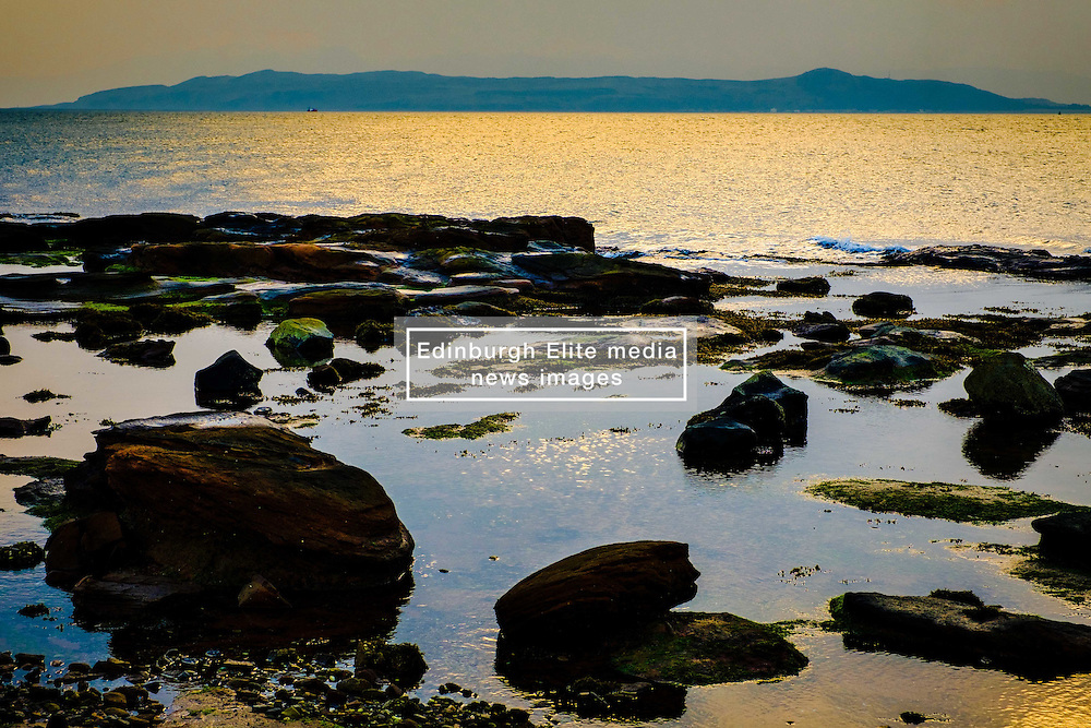 Evening light on the rocks at Little Skate Bay on the west coast of the island of Great Cumbrae, Scotland.  The Isle of Bute can be seen in the background.<br /> <br /> (c) Andrew Wilson | Edinburgh Elite media