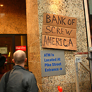 A sign is affixed to the Bank of America in Westlake Park during the Occupy Seattle protest on Saturday, October 15, 2011 in Seattle. About 5,000 people joined protesters that have been camped at Westlake Park for two weeks. The demonstration is an offshoot of the Occupy Wall Street protest in New York. Saturday was dubbed as a global day of action by the movement. (Joshua Trujillo, seattlepi.com)