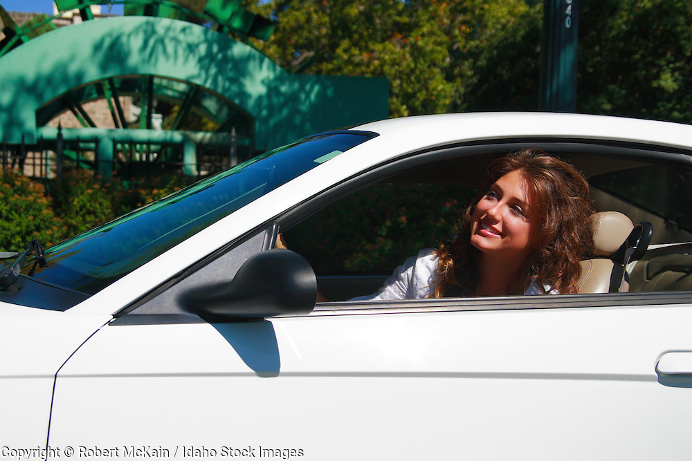 IDAHO. Boise. Young woman seated in sports car, smiling. September 2008. #pa080301  MR