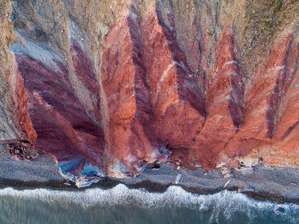 Canada, Newfoundland, Codroy, Aerial view of waves breaking below red cliffs along Atlantic Ocean shoreline on summer evening