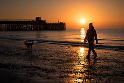 © Licensed to London News Pictures. 06/11/2017. Southsea, UK.  A woman walking her dog along the beach during sunrise in Southsea this morning, 6th November 2017. Photo credit: Rob Arnold/LNP