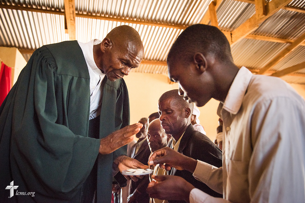 The Rev. Stanford Soko, vice diocesan chairman of the Confessional Lutheran Church–Malawi Synod, distributes the sacrament to parishioners during worship on Saturday, Sept. 26, in Embangweni, Malawi. LCMS Communications/Erik M. Lunsford