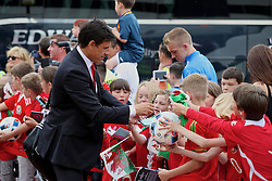 CARDIFF, WALES - Saturday, June 4, 2016: Wales' manager Chris Coleman signs autographs for school children as the team arrive at Cardiff Airport ahead of the team's departure to Sweden and onto the European Championships 2016 in France. (Pic by David Rawcliffe/Propaganda)