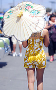 A woman dressed in 50's style walking away holding a paper oriental umbrella, Viva Las Vegas Festival, Las Vegas, USA 2006.