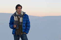Asian American man in winter clothes holding a camera in the desert