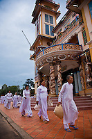Female worshippers walking in front of the Holy See in Tay Ninh.