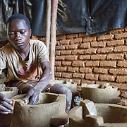 CAPTION: Phuka Phuka Stove Production Group member Alex Blessings, hard at work. Stove production groups like this one are proving to be good for local economies, as demand continues to outstrip supply for a product that brings the typical low income household considerable savings. LOCATION: Phuka Phuka Stove Production Group, Area 36, Lilongwe, Malawi. INDIVIDUAL(S) PHOTOGRAPHED: Alex Blessings.