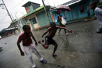 Boys play in the rain in Lleras, a poor barrio in Buenaventura, on the Pacific Coast of Colombia, on Sunday, May 13, 2007. Buenaventura is in the midst of a spree of violence over control of drug shipments from the poor barrios in the city. Many of the neighborhoods have a strong presence of FARC militias that control most of the drug trade in the city. (Photo/Scott Dalton)