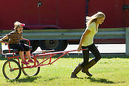 Middletown, New York - One girl pulls another in a carriage at The 70th annual Middletown Rotary Horse Show at Fancher-Davidge Park on Sept. 8, 2013. The carriage was being used for pony rides.