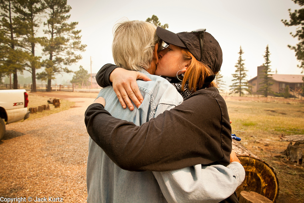 """05 JUNE 2011 - GREER, AZ:  Kristi Spillman (CQ) says goodbye and kisses Bob Cline (CQ), a friend in Greer Sunday. Spillman operates the Frosty Bottom Cafe and Cline the """"Quacker Barrel"""" (CQ QUACKER). The fire grew to more than 180,000 acres by Sunday with zero containment. A """"Type I"""" incident command team has taken command of the fire.  PHOTO BY JACK KURTZ"""