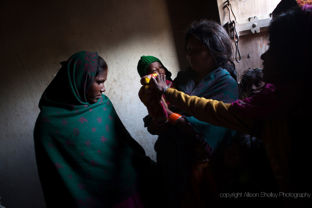 Pratima Devi, left, 15, looks on as a neighbor plays with a baby at the home where Pratima lives with her husband's family in Mastpura in the state of Bihar, India.  Pratima's first child was born prematurely five weeks ago and died two days afterwards.